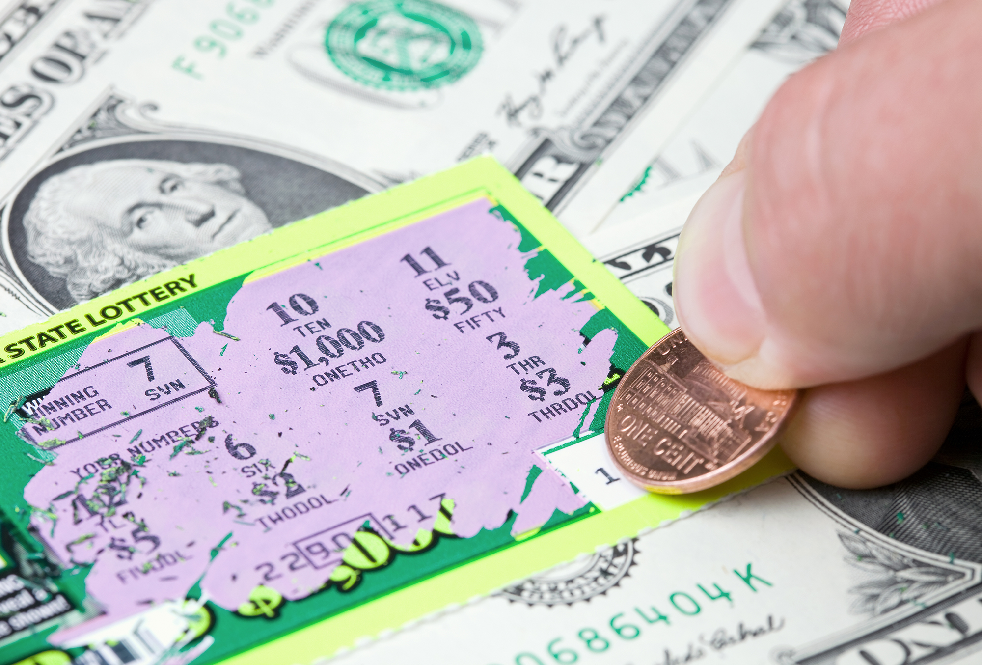 """""""A lottery player has scratched a winning ticket which rests on a dollar bill background. The 7 in the Winning Number box matches the 7 mid-frame, resulting in a $1.00 win.A related image from my portfolio:aA"""""""