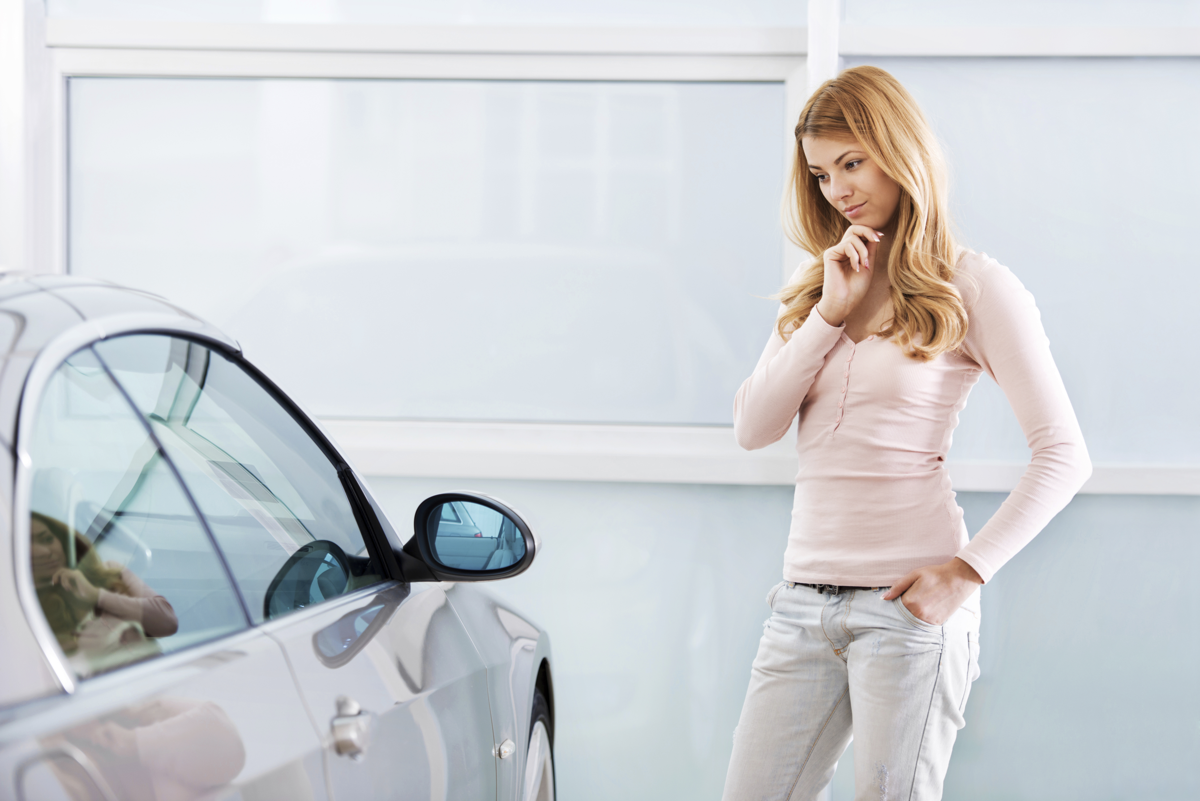 Young woman thinking to buy a car in a showroom.