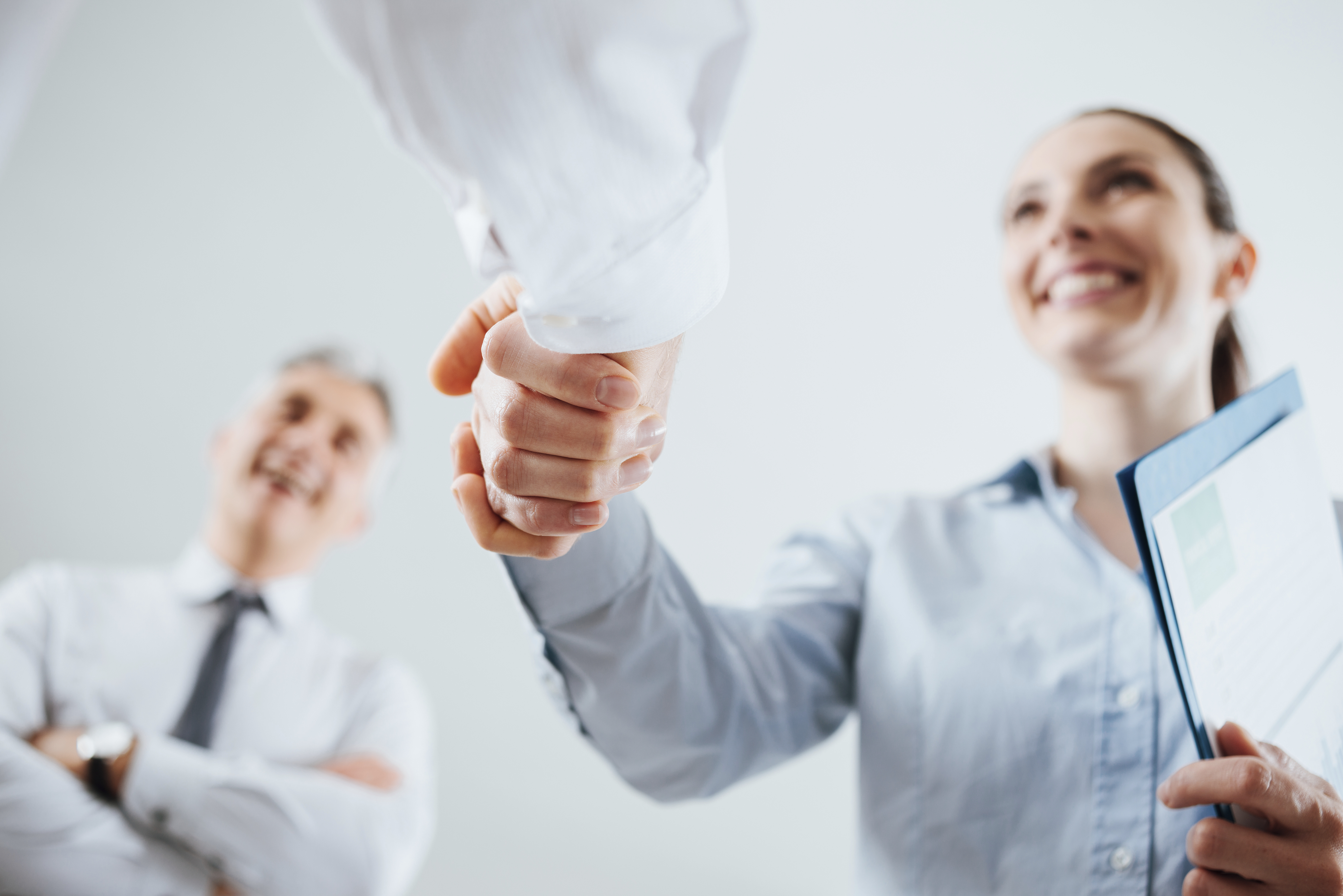 Confident business people shaking hands and woman smiling, recruitment and agreement concept