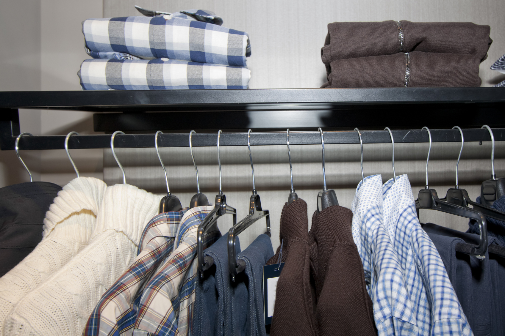 Close up of row of male clothes on hangers and folded on rack. Shirts, jeans,trousers,pullovers.